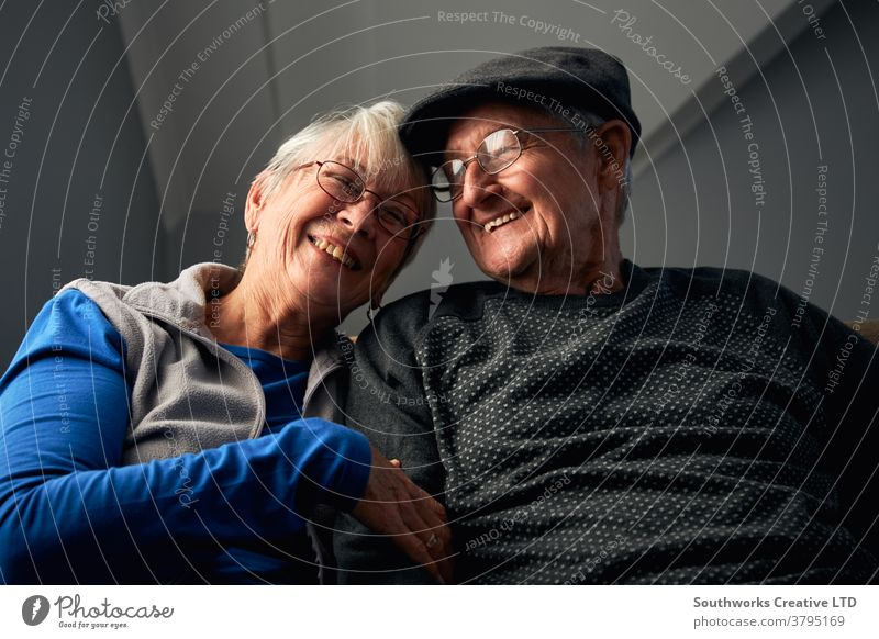Laughing Senior Couple Sitting On Sofa At Home Watching Television Together couple senior seniors retired at home watching tv television sitting sofa together