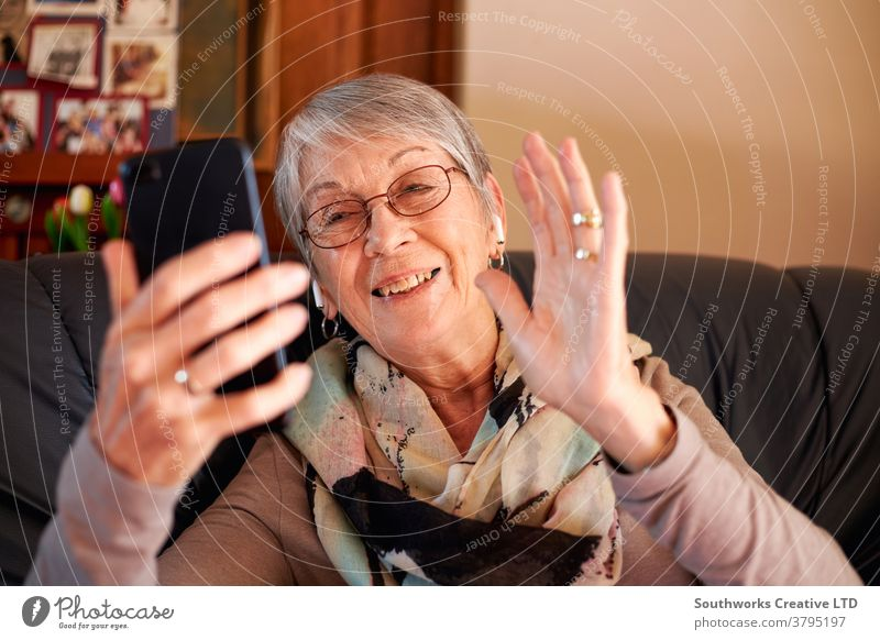 Smiling Senior Woman At Home Waving As She Makes Video Call To Family On Mobile Phone senior woman video call video chat mobile seniors cell at home
