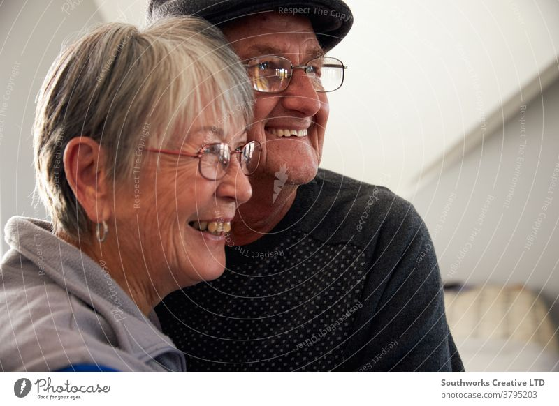 Loving Senior Couple Laughing And Smiling As They Hug Each Other At Home Together couple senior seniors retired at home relaxing standing window loving