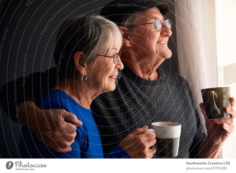 Loving Senior Couple Relaxing And Chatting Standing By Window At Home Together With Hot Drink couple senior seniors retired at home relaxing standing window