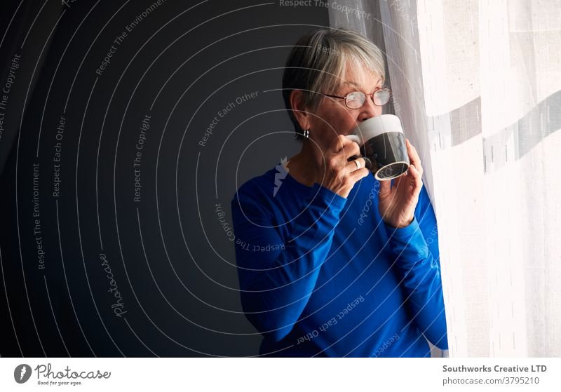 Senior Woman Relaxing Standing By Window At Home With Hot Drink woman senior seniors retired at home relaxing standing window drink drinking hot drink