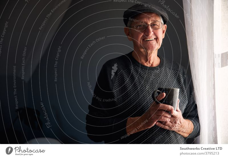 Portrait Of Senior Man Wearing Cap Relaxing Standing By Window At Home With Hot Drink man senior seniors retired at home relaxing standing window drink drinking