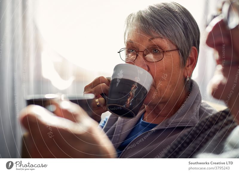 Senior Couple Relaxing And Chatting On Sofa At Home Together With Hot Drink couple senior seniors retired at home relaxing sitting sofa talking chatting drink