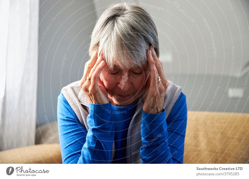 Senior Woman Suffering With Stress Or Headache At Home Holding Head In Pain senior seniors woman at home headache migraine health pain holding stress stressed