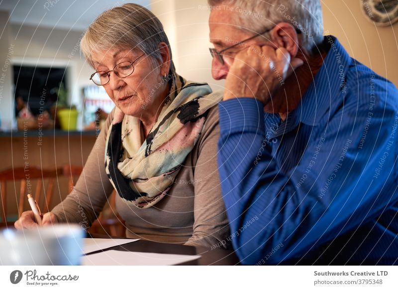 Senior Couple At Home Sitting At Table Checking Personal Finances couple senior seniors retired at home shopping buying choosing checking holiday finance