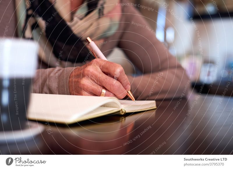 Close Up Of Senior Woman At Home Sitting At Table And Writing In Notebook Or Journal senior seniors woman at home writing diary journal making list making notes