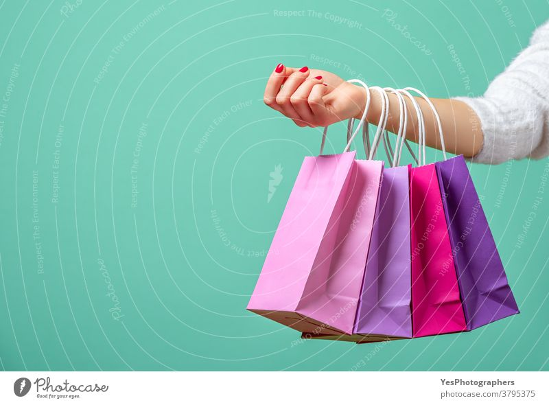 Shopping bags on womans hand. Woman shopping with colored paper bags. alone aqua arm background black friday blue buy carrying christmas close-up colorful
