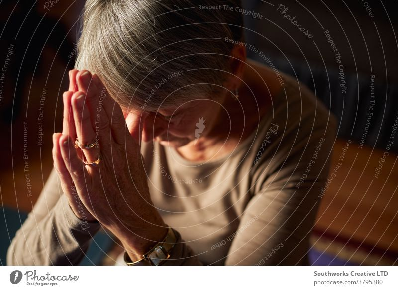 Close Up Of Senior Woman At Home Praying Or Meditating With Hands Together senior woman praying religious prayer seniors at home religion faith belief
