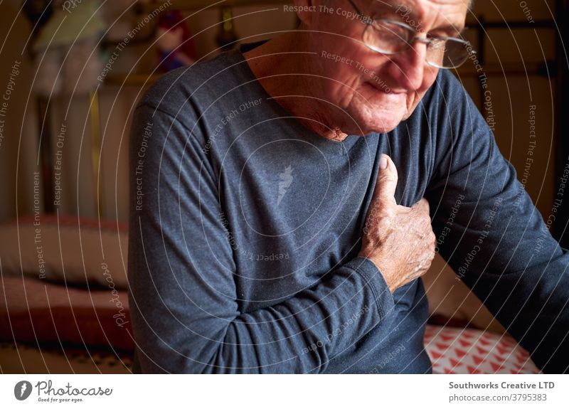 Senior Man With Health Issues At Home Clutching Chest In Pain senior man holding chest pain heart attack seniors at home health clutching ill illness sick