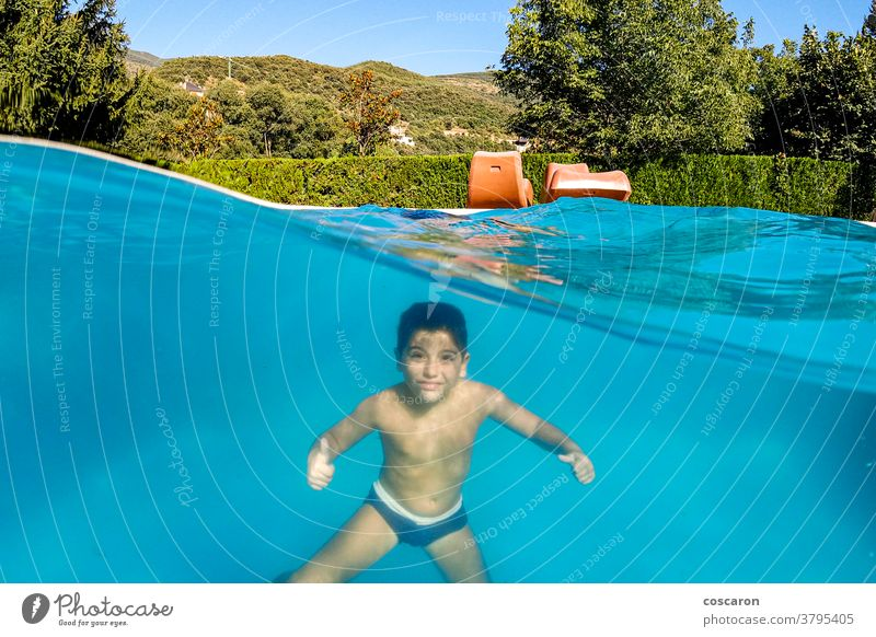 Funny boy diving on a swimming pool active aquatic blue caucasian cheerful child childhood clear cute dive dome enjoy enjoying enjoyment excited expressions