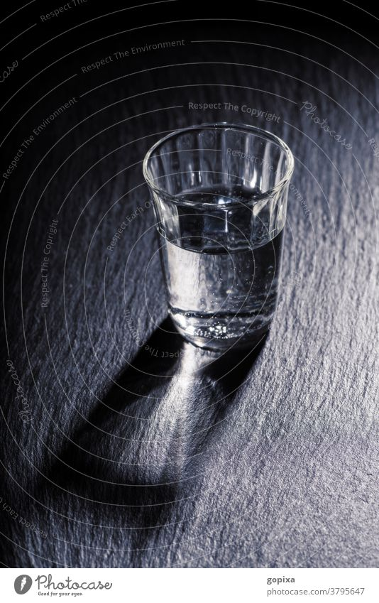 A glass of water with shadow Glass drinking glass Water Drinking water Mineral water Food food products Healthy Thirst Simple Dark darkness Sparse Shadow