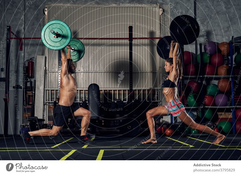 Determined young athletes lifting barbells and doing lunges in gym woman workout exercise sport healthy endurance power intense functional training sportsman