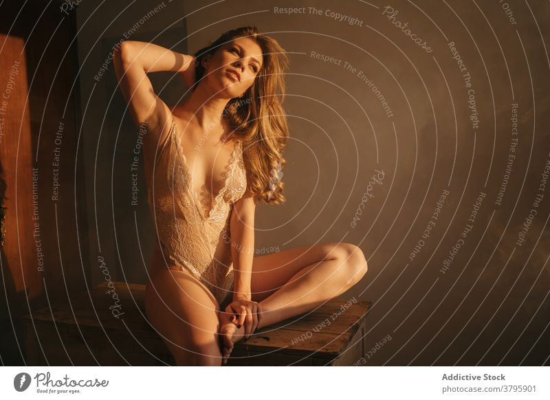 Seductive woman in bodysuit in room lace slender sensual lingerie curve grace gorgeous seductive female barefoot wooden table tranquil slim underwear perfect
