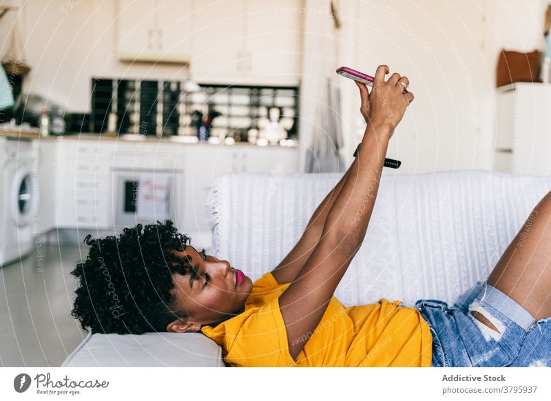 Laughing black woman taking selfie with smartphone at home using laugh having fun excited browsing mobile cheerful millennial young adolescent female modern