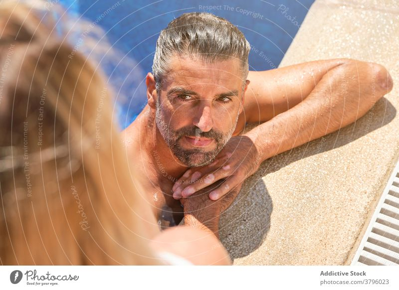 Content man relaxing in pool during summer holidays vacation content girlfriend together resort relationship recreation male adult gray hair beard enjoy travel