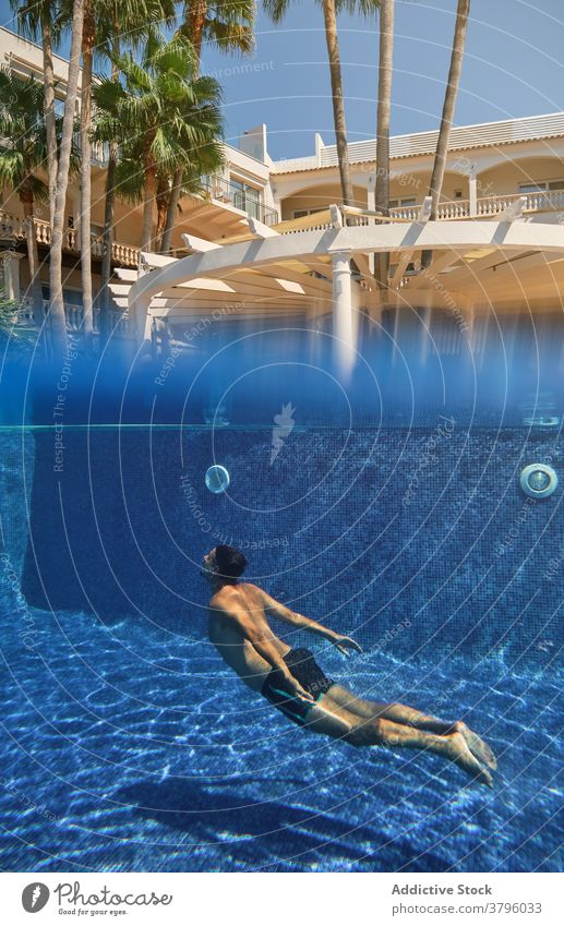 Unrecognizable person diving into swimming pool dive underwater summer resort holiday refreshment tropical activity splash transparent vacation travel