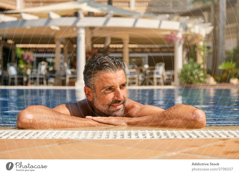 Relaxed man chilling in swimming pool in resort summer happy enjoy travel relax poolside vacation male beard ethnic adult handsome tropical holiday rest