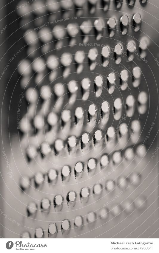 detailed monocrome macro shot of a metal cheese grater blade cook rectangular cooking diet kitchen over rub shiny chef retro cuisine abstract food sharp