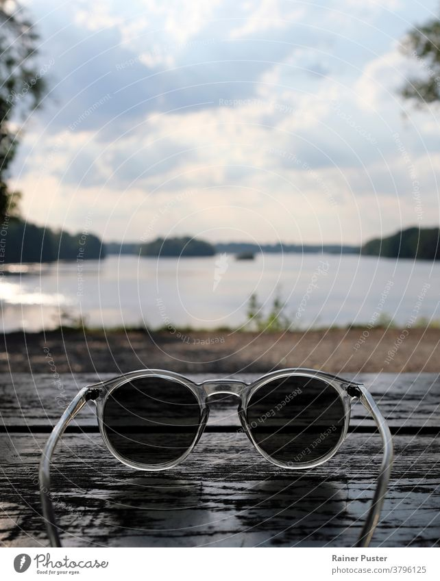 Beautiful lake seen behind a pair of sunglasses accessory background copy space eyeglasses looking through sunglasses personal perspective point of view pov