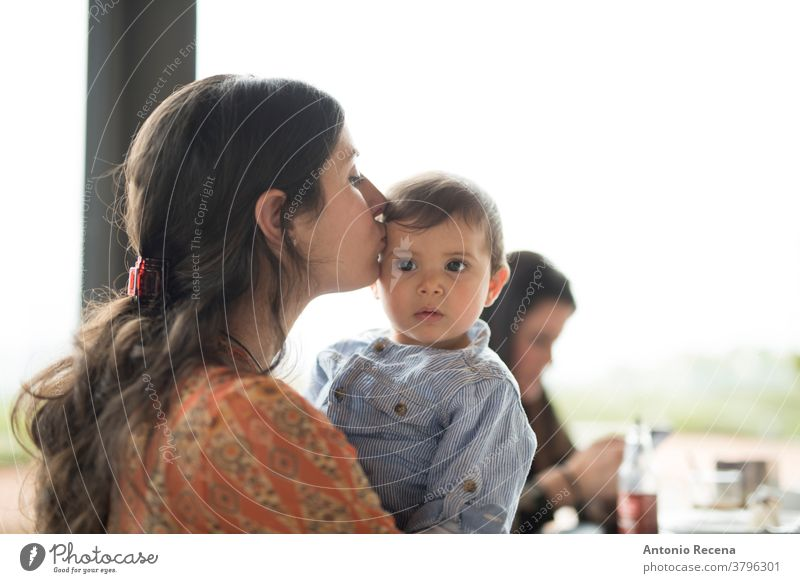 mother kissing little baby at bar terrace mother's day son restaurant love lifestyles people women woman kid child children boy care parent mothers day spanish