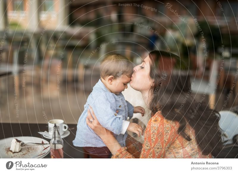mother kissing little baby at bar mother's day son restaurant love lifestyles people women woman kid child children boy care parent mothers day spanish