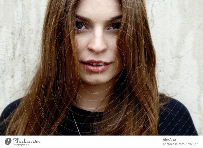 Close portrait of a young woman in front of a concrete wall Woman Young woman 18-25 years warmly pretty Charming Slim Brunette long hairs Fresh Large smart