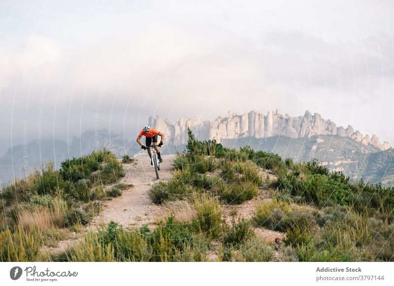 Active man with bicycle in hilly terrain cyclist mountain bike active sport ride nature male helmet adventure transport travel extreme freedom vehicle lifestyle