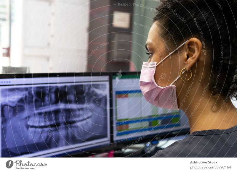 Ethnic dentist in mask examining X ray in hospital x ray examine dental teeth woman doctor stomatology monitor computer female ethnic black african american