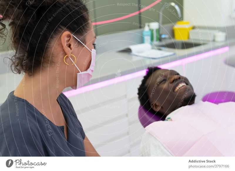 Smiling black dentist and patient in medical room doctor treat procedure dental dentistry stomatology ethnic african american mask cheerful professional