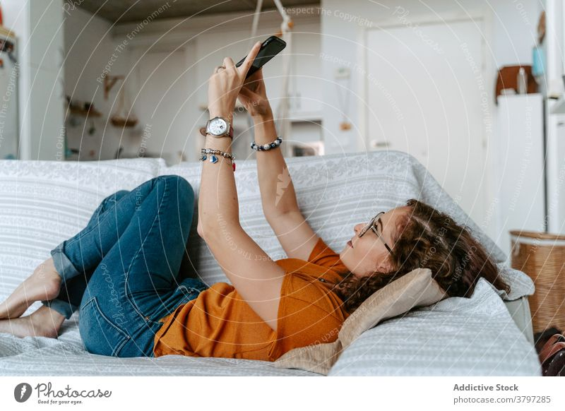 Young female taking self portrait on smartphone lying on sofa woman selfie relax social media comfort using gadget home device lazy young casual ginger hair