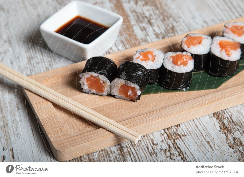 Sushi rolls with salmon on wooden board sushi hosomaki japanese food seafood fish tradition set fresh meal cuisine dish gourmet oriental asian chopstick serve