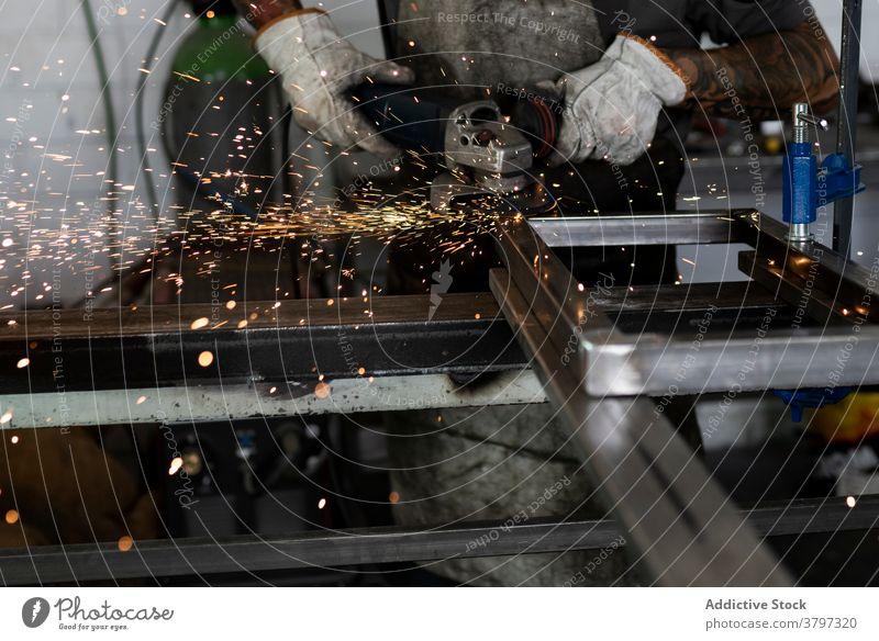 Male worker using electric grinder in workshop machine man cut welder metalwork spark male detail industry instrument skill tool manufacture equipment