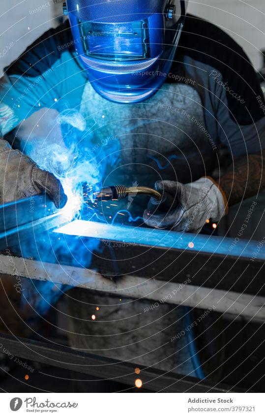 Professional welder in protective helmet in workshop metal man machine dark spark light male worker occupation professional tool industry job equipment labor