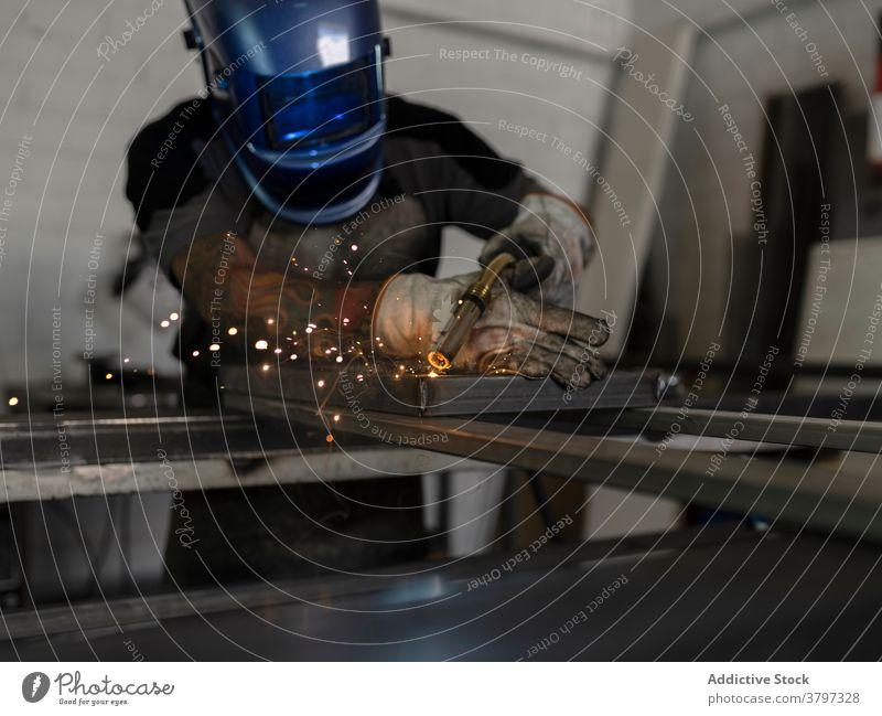 Factory male worker producing metal construction weld machine welder man metalwork process spark workbench factory equipment industry tool occupation detail