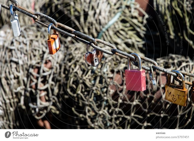 Six love - locks hanging on a chain in front of a fishing net Lock Chain Love Padlock Infatuation Together Metal Emotions Heart Rust Net Fishing net