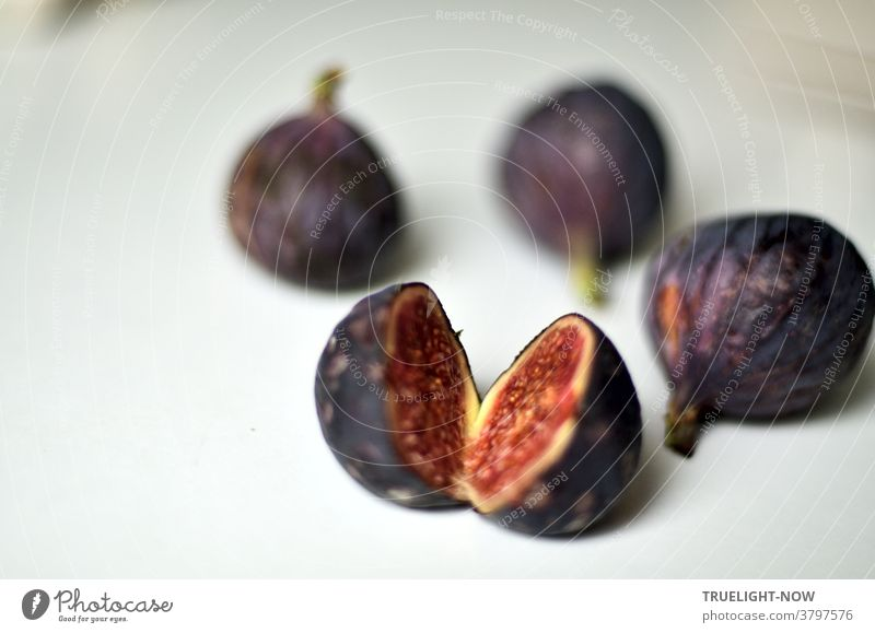 Fresh, ripe figs in a dark blue violet skin, one of them cut open showing its red flesh, lying on a white table in bright daylight Figs Mature fruits Blue Red