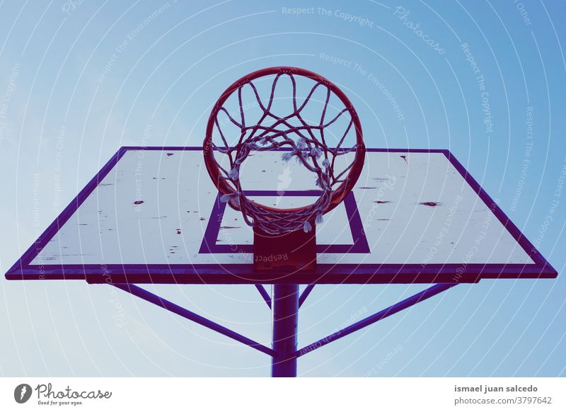 street basketball hoop  and blue sky silhouette circle chain metallic net sport sports equipment play playing playful old park playground outdoors minimal
