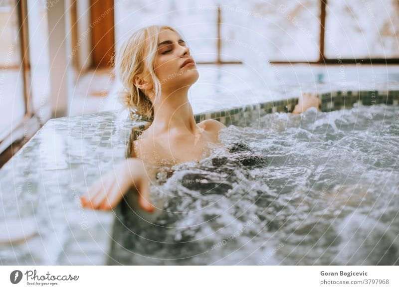 Young woman relaxing in the whirlpool bathtub adult beautiful beauty body bubble caucasian enjoying female health healthy hot hydrotherapy leisure lifestyle one