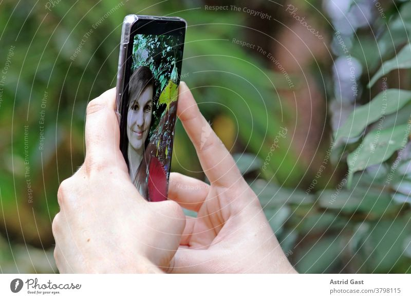 A young woman takes a self-portrait with her smartphone. A selfie with her mobile phone Woman Cellphone photo Selfie Self portrait Take a photo yourself
