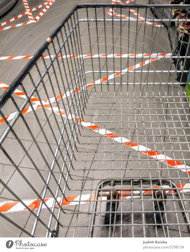 Empty shopping trolley in the checkout area with umpteen barrier strips stuck to the floor | Corona | Everyday life during the pandemic|