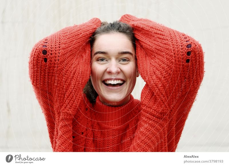 Close portrait of a laughing young woman with dimples in front of a concrete wall Woman Young woman 18-25 years warmly pretty Charming Slim Brunette long hairs
