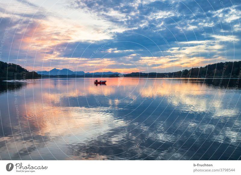 single fishing boat at the lake at dusk Fishing boat Evening Dusk Sunset Twilight Silhouette Landscape Clouds Sky Nature Exterior shot Horizon Fisherman