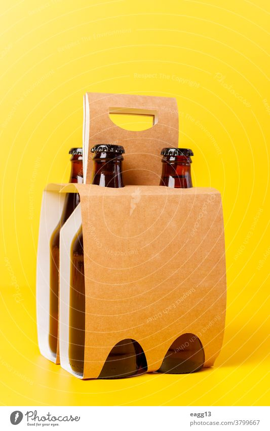 Presentation of pack of four beers with yellow background ale bavarian belgian beverage booze bottle bottles box brand branding brewery carton case container