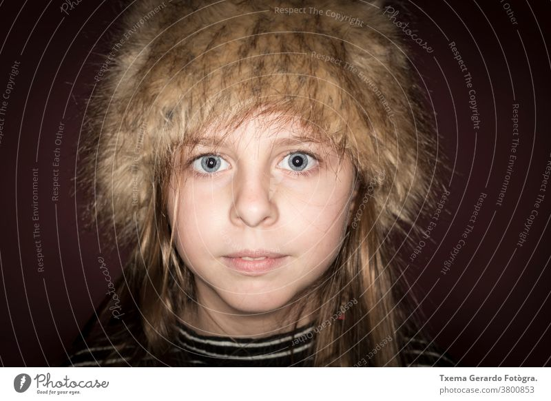 Studio portrait of a cute girl with long blonde hair wearing a winter hat against brown background pretty girl studio portrait european caucasian blue eyes