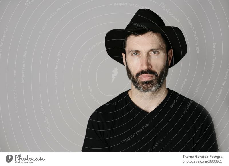 Close-up portrait of a handsome bearded middle-aged man with hat against neutral background studio confident grey guy face isolated adult lifestyle cool indoors