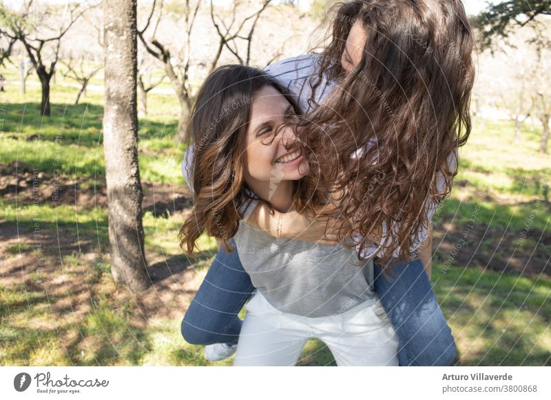 two girls a park of almond trees laughing together, climbed one on top of the other activity background beautiful bright careless cheerful colorful female