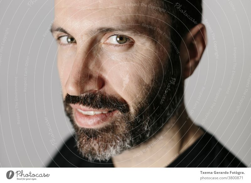 Close-up portrait of a handsome bearded middle-aged man against neutral background studio confident grey guy face isolated adult lifestyle cool indoors mature