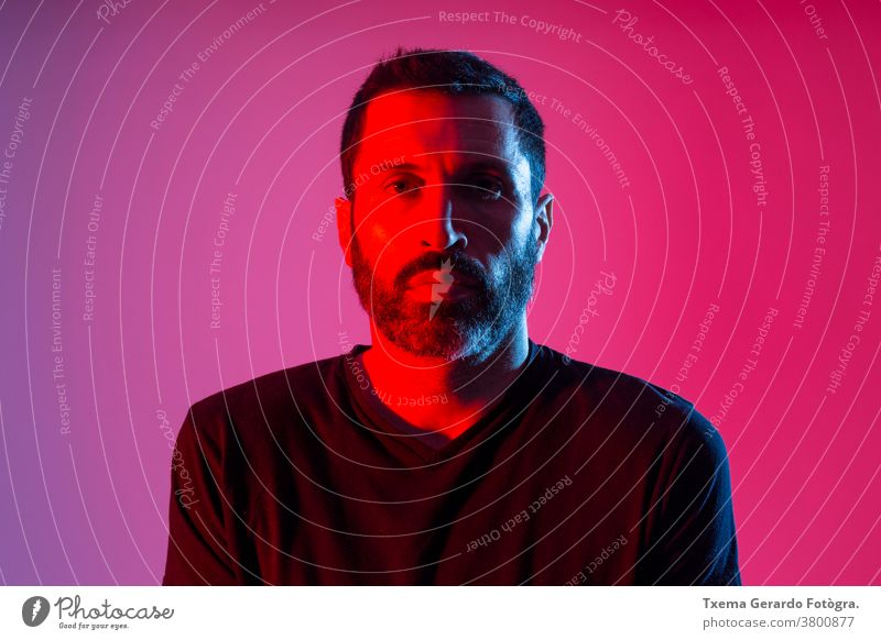 Colorful studio portrait of a bearded man against red and blue background. facial expression colored front view colorful dark sweatshirt art model adult face
