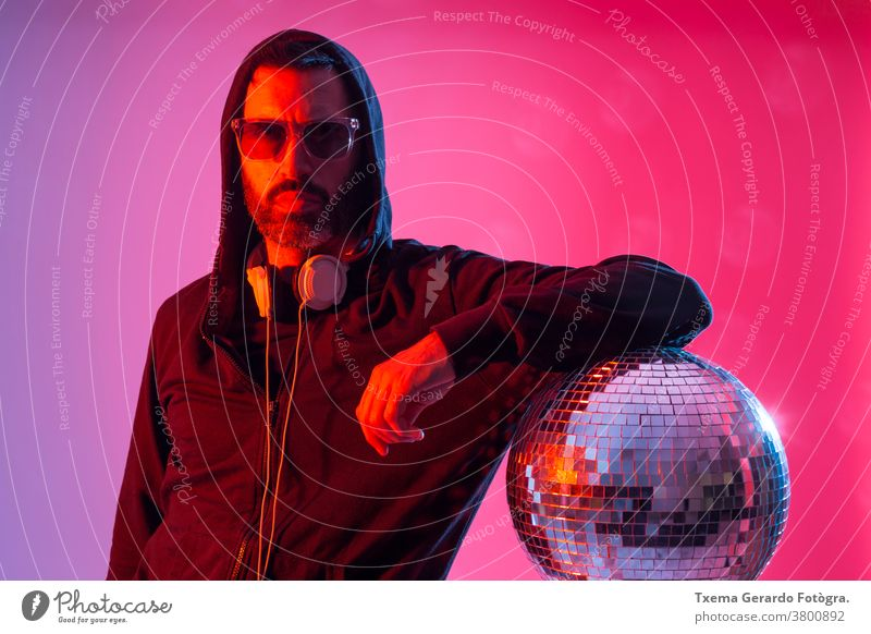 Colorful studio portrait of a bearded deejay with headphones and sunglasses against red and blues background. disco music colored pop sound disco ball mirrors