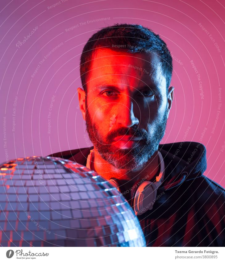 Colorful studio portrait of a bearded deejay with headphones against red and blues background. disco music colored pop sound disco ball mirrors clubbing